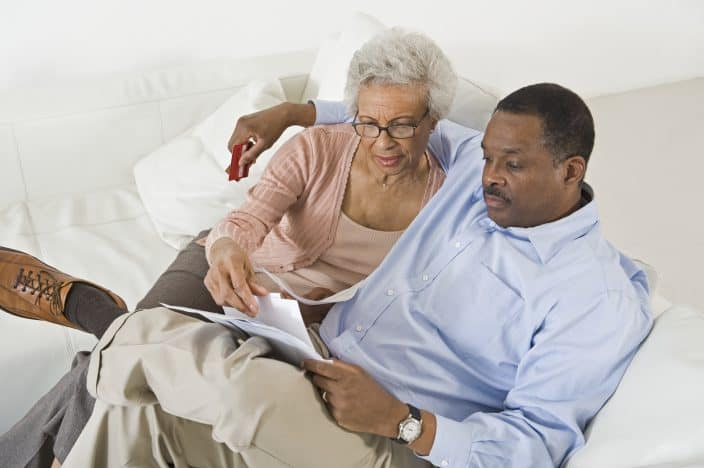 black man and black woman sitting down on sofa discussing finances