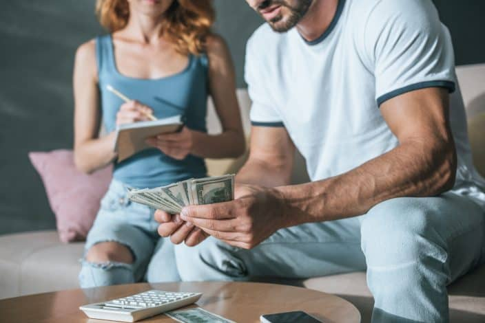 Couple counting money in the living room and budgeting