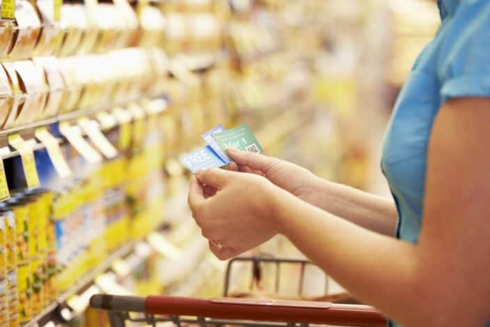 woman in grocery aisle using coupons to save money