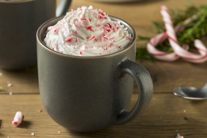spiked hot chocolate candy cane topped with whipped cream