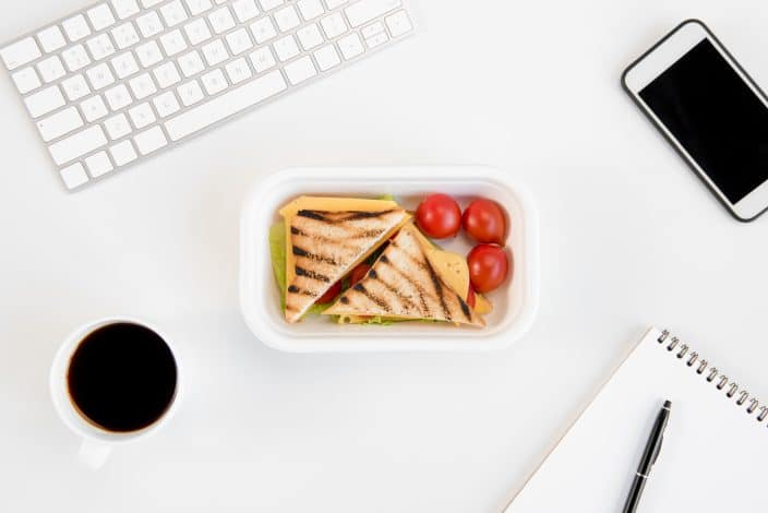 Top view of sandwiches with tomatoes in lunch box, notebook with pen, cup of coffee, smartphone and keyboard at workplace in order to cut eating out expenses