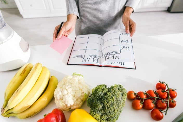 woman making a meal plan in notebook with a sticky note to help budget