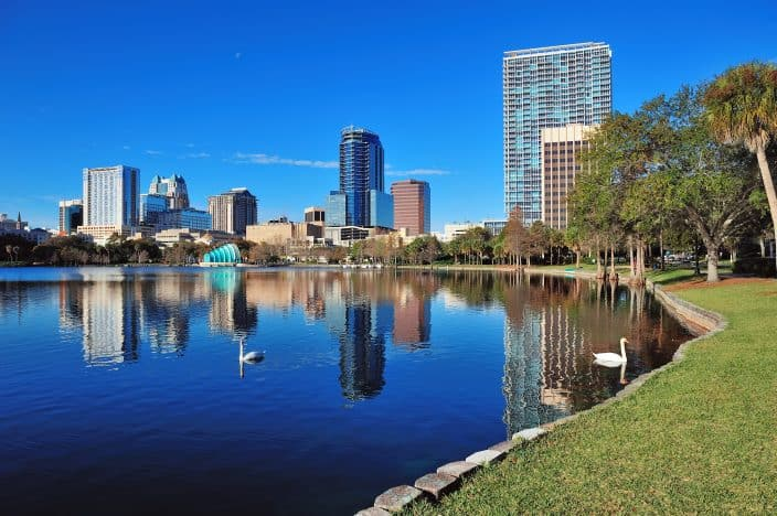 a lake in orlando with sky scrapers in the background