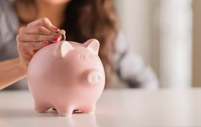 woman putting coins into a piggy bank for saving