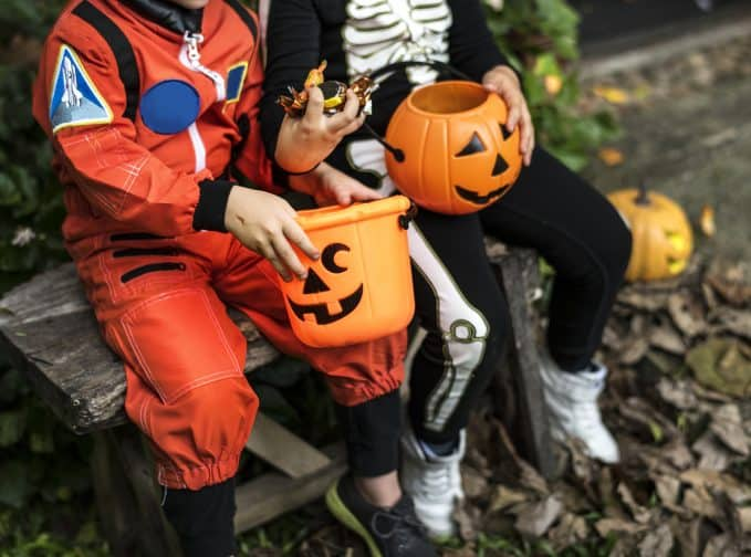 children in costumes sitting with candy after trick or treating as a free activity