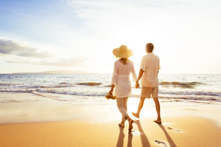 a couple walking on the beach with golden sand, bright sun and glistening waters. A perfect romantic getaway in the South