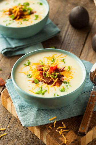 loaded cauliflower soup topped with bacon, green onions and cheese in a blue bowl on a wooden cutting board