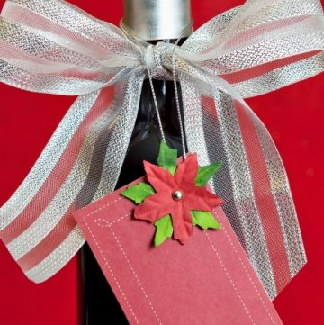 gift bottle of wine with red tag and red and white bow on red background is a great wine lovers holiday gift