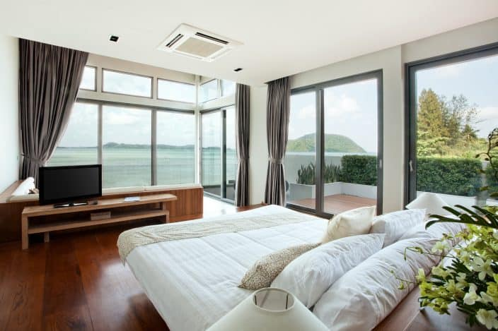 a hotel room with large windows greenery and wooden floors with a view of the water