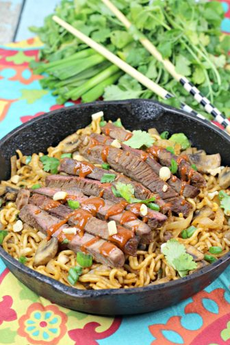 Spicy Korean beef with ramen noodles in a cast iron skillet on a table with chopsticks and parsley and green onion in the background