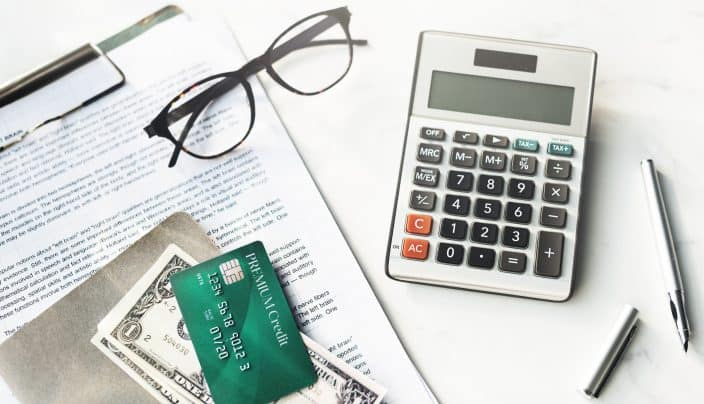 A calculator, papers, credit card, dollar bills, and glasses to be used for calculating and reducing debt