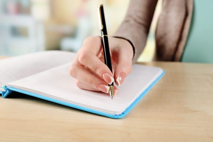 a female hand writes in a notebook on a table to make a list of her debts