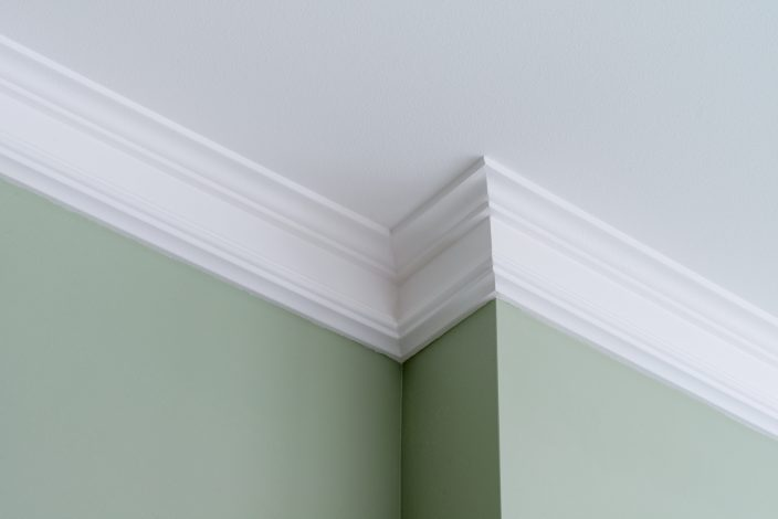 Ceiling moldings in the interior, a detail of intricate corner with green walls