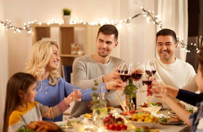 happy family having dinner party, drinking red wine and toasting at home with a meal made in a slow cooker