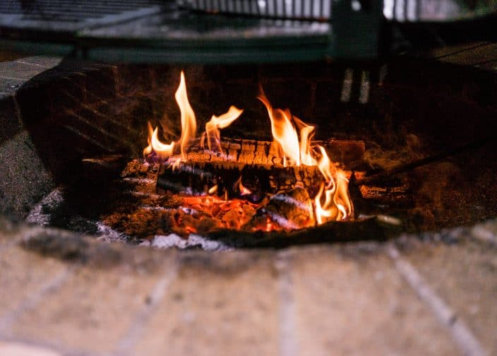 a close up shot of a fire in a brick fire pit an activity you can do to celebrate new years eve 2020