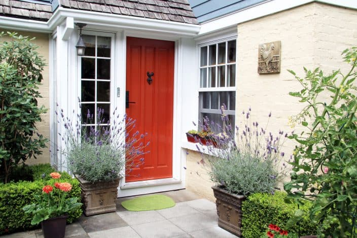 a house with a red front door and a garden