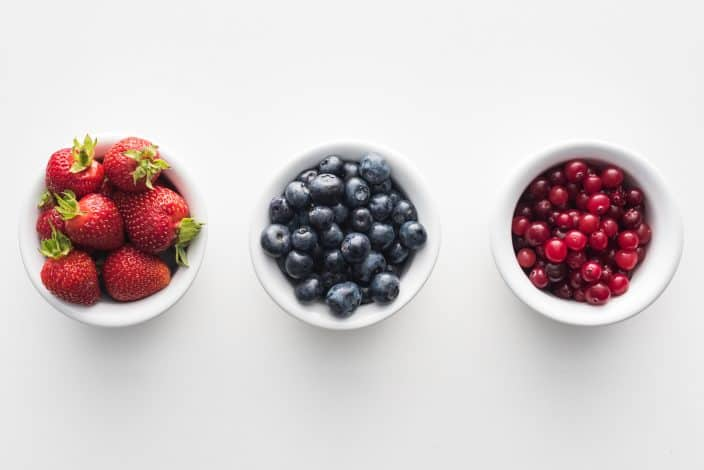 strawberries, blueberries, and cranberries in separate bowls to use as a topping for rice pudding