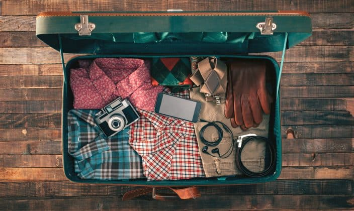 traveler packing, open suitcase on a wooden table with clothing, camera and mobile phone