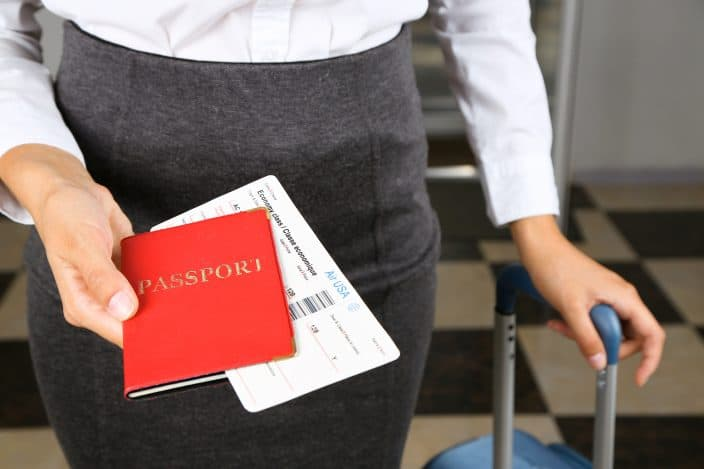 Woman with suitcase holding passport  and tickets making sure to have essential items handy