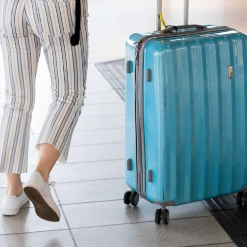 Blue suitcase with woman in striped pants