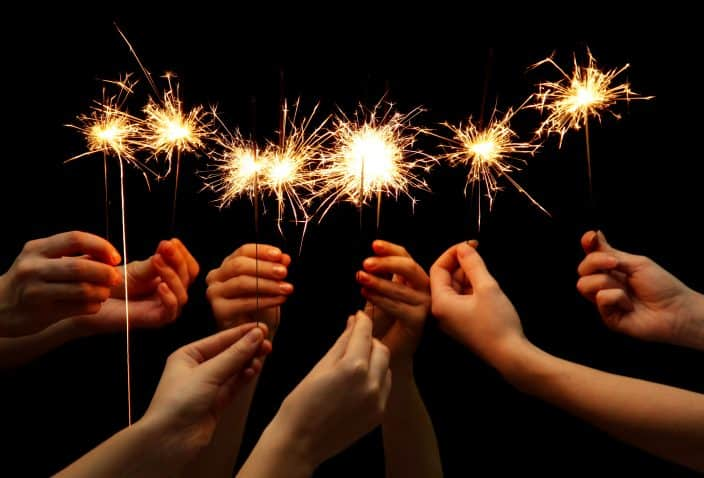 sparklers held in hands as a way to celebrate New Years Eve at home