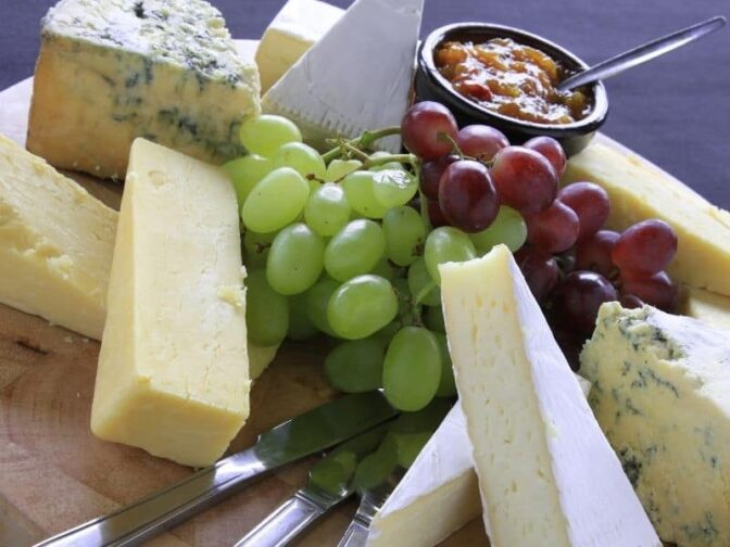 selection of cheeses and fruits on a wood platter to put on a cheese board for holiday entertaining