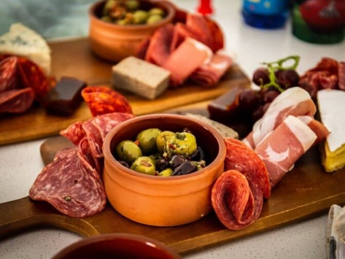 meat, cheese, and olives on a charcuterie platter