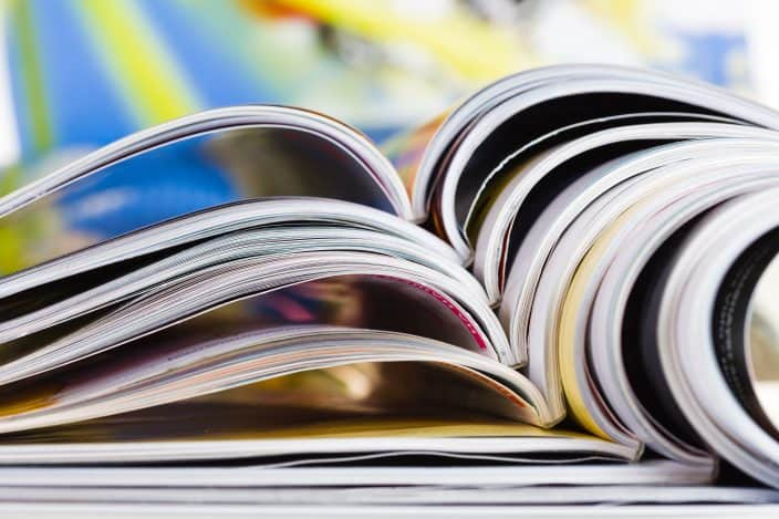 Closeup background of a pile of old magazines with bending pages to use for making a vision board