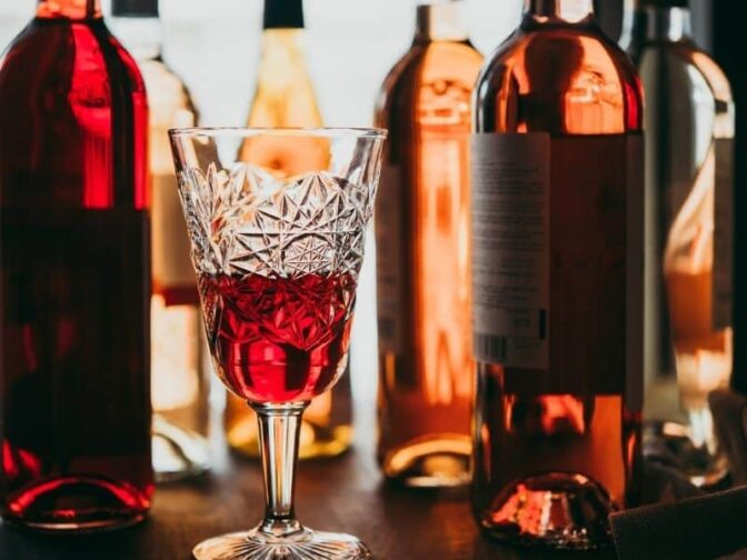 selection of wines with a crystal wine glass with red wine to serve during holiday entertaining