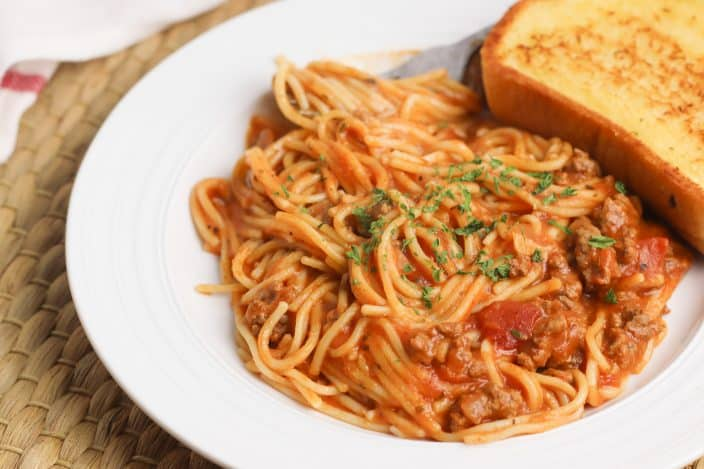 spaghetti and meat sauce on a white plate garnished with parsley