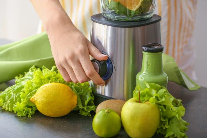 a woman preparing a green smoothie with apples, lemons, and greens