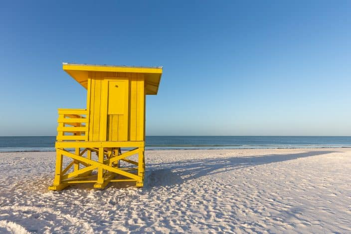 yellow life guard stand on a white beach with blue water and skies, siesta key