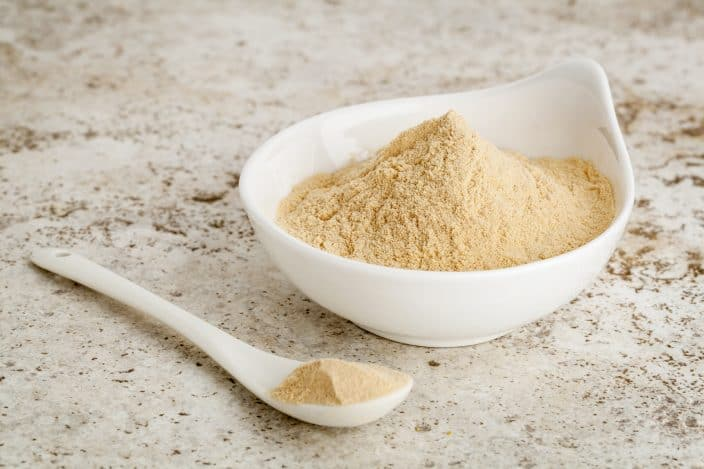 maca root powder a healthy addition for a smoothie - a small bowl with a spoon against ceramic tile surface