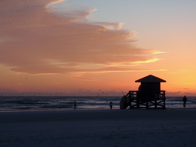 Siesta Keys beach sunset with a flock of birds flying by, people photographing the event and a lifeguard tower