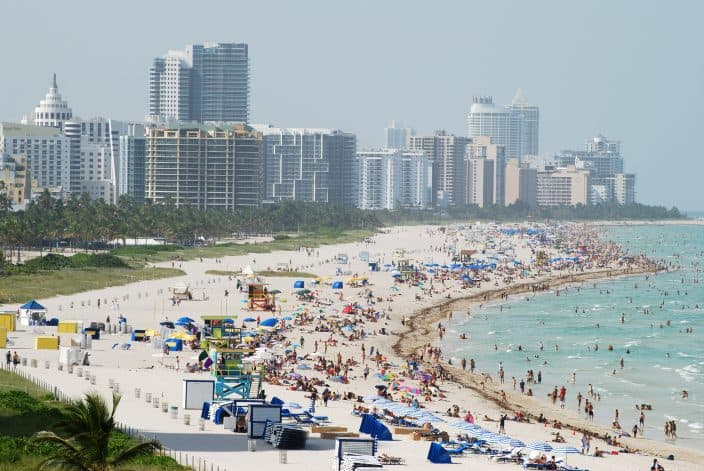 The view of southernmost part of Miami South Beach (Florida) with lots of people on the beach, high rises and misty skies.