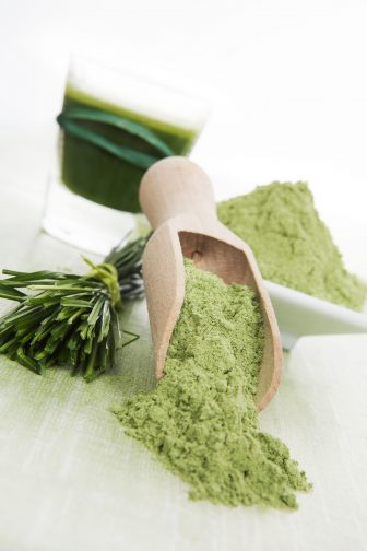 wheatgrass powder, fresh and juiced against a white background. A good addition to a smoothie