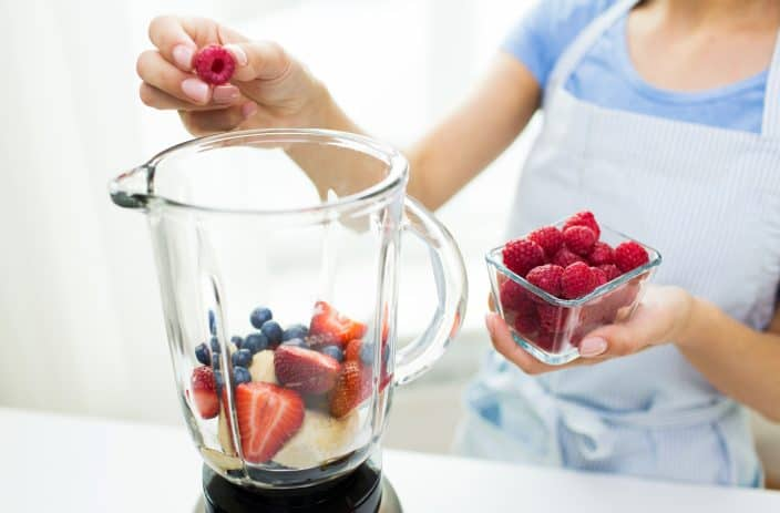 a woman putting berries into a blender to make a smoothie