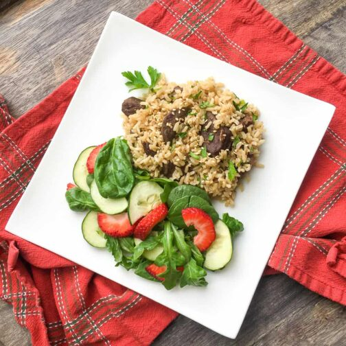 Asian beef and rice on a white plate with a strawberry, cucumber, and spinach side salad