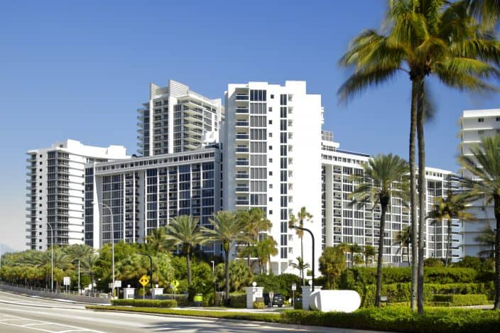 Bal Harbour high rises in Miami with blue skies and palm trees
