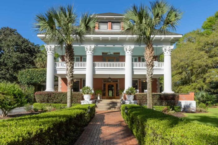 The Herlong Mansion outdoor view of the front in Florida with blue skies and palms