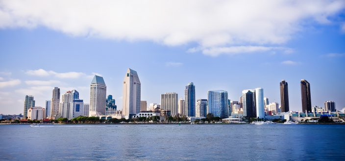 San Diego city skyline at sunset, showing the buildings of downtown rising above harbor viewed from Coronado Island. One of the best cities to retire in.