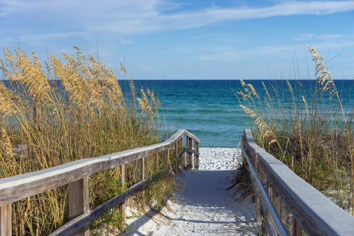 Sandy boardwalk path to a snow white beach on the Gulf of Mexico with ripe sea oats, the perfect location for a romantic spa weekend getaway