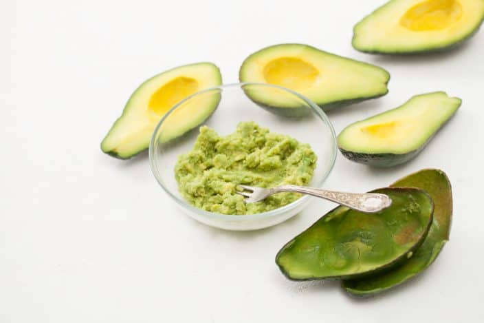 avocado spread with empty and whole avocados