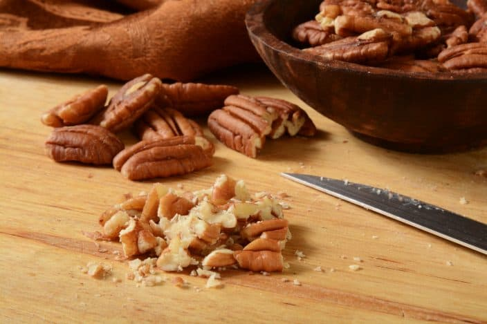 close up of chopped pecans on a cutting board for the making of possum pie