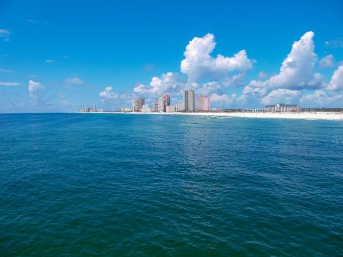 blue water view of orange beach, Alabama with hotels on the shore line