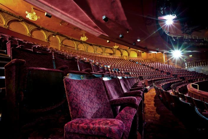 Rows of empty seats in an empty theatre auditorium.