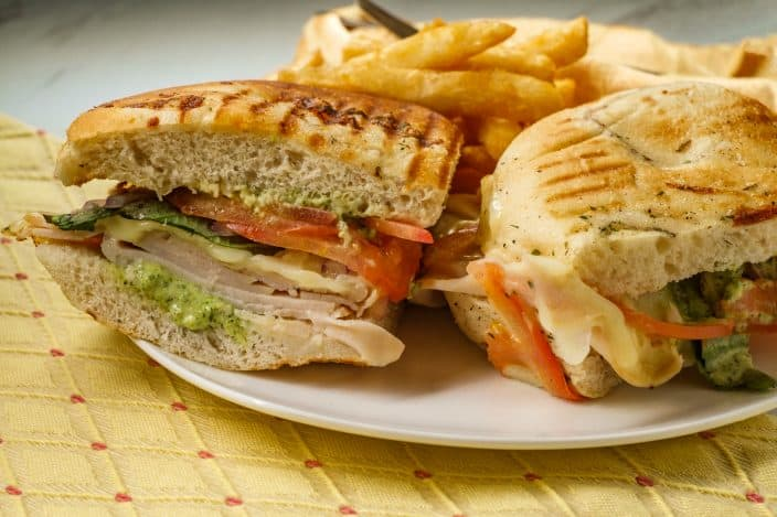 a finished turkey pesto sandwich cut in half on a plate with french fries