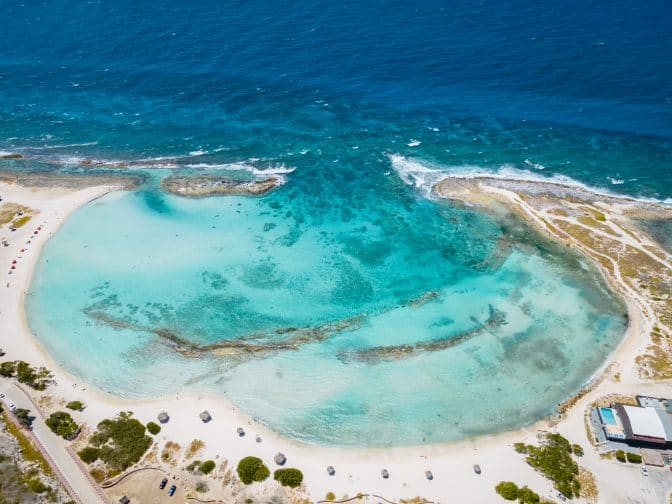 An aerial view of Baby Beach, with white sands and blue ocean, one of the best beaches in Aruba.
