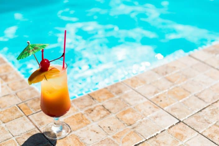 mai tai cocktail with a festive umbrella, orange slice, and cherry on tile by the pool