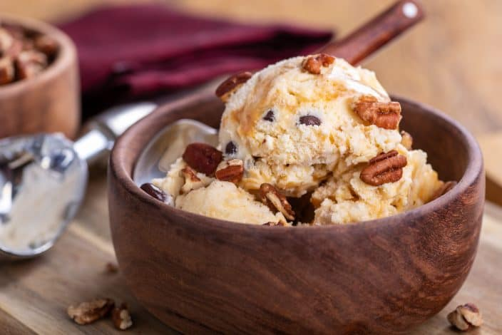 no churn salted caramel and pecan ice cream in a wooden bowl with a spoon